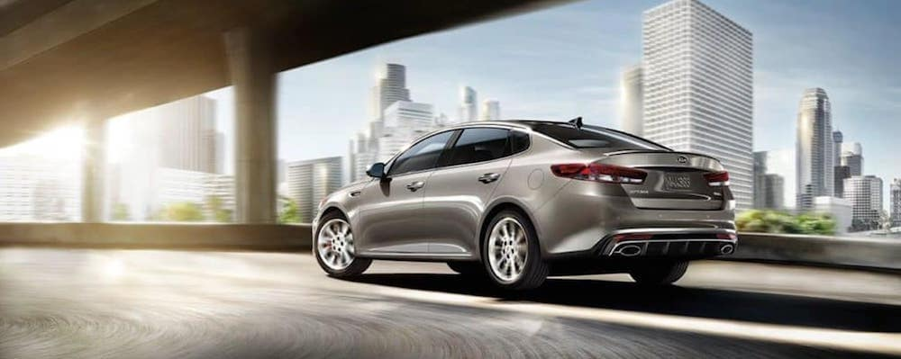 Silver Kia Optima driving in a city
