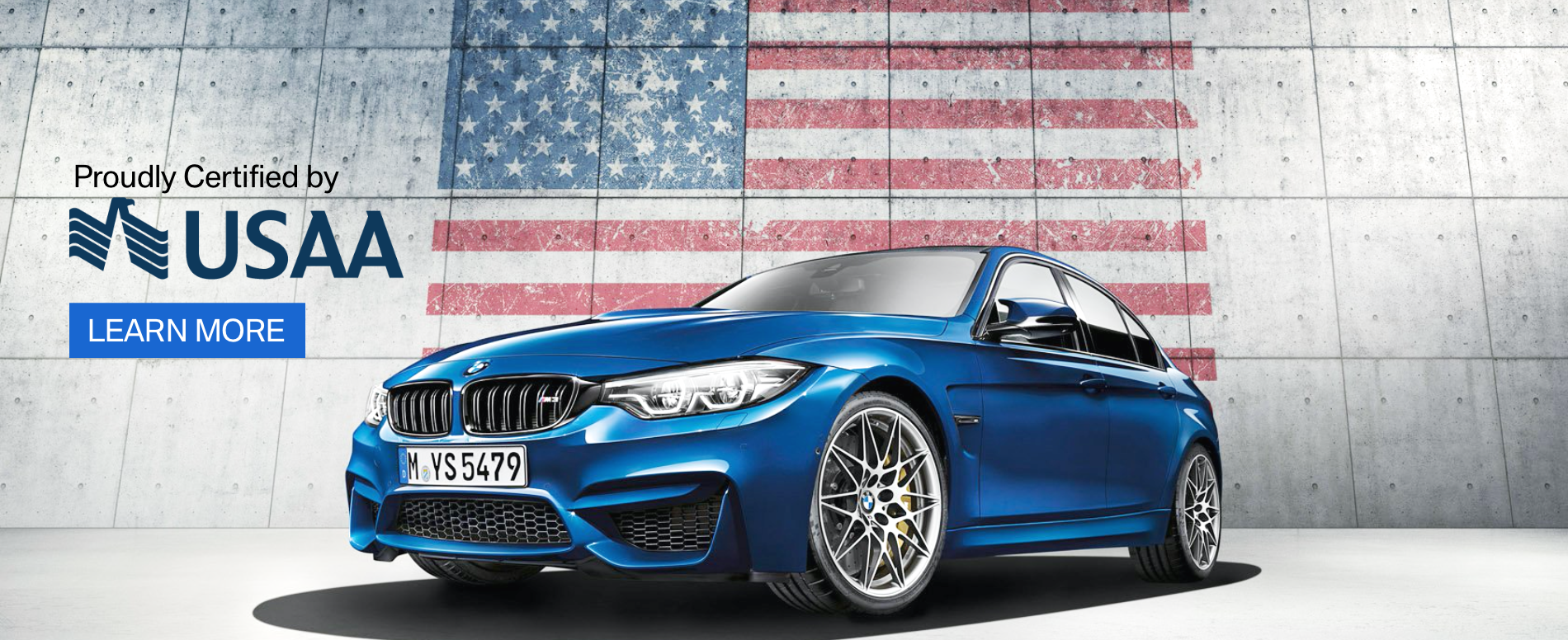 A BMW on display in front of an American Flag, showing the USAA logo in support of our military.