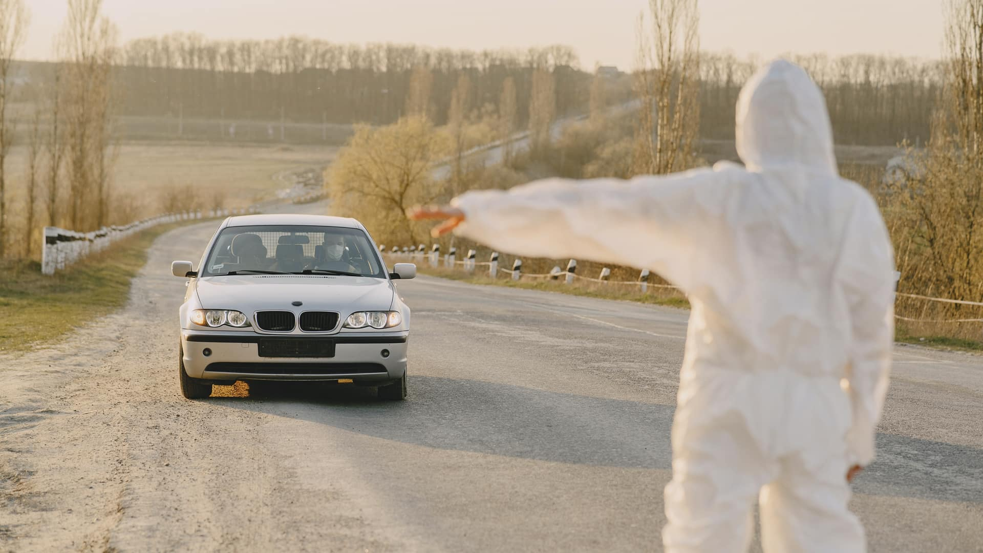 Photo of a man in a hazmat suit stopping a white BMW with a person wearing a mask.