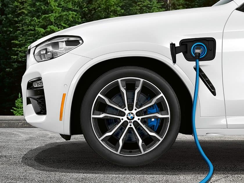 BMW X3e plug-in hybrid connected to a charger on the road.