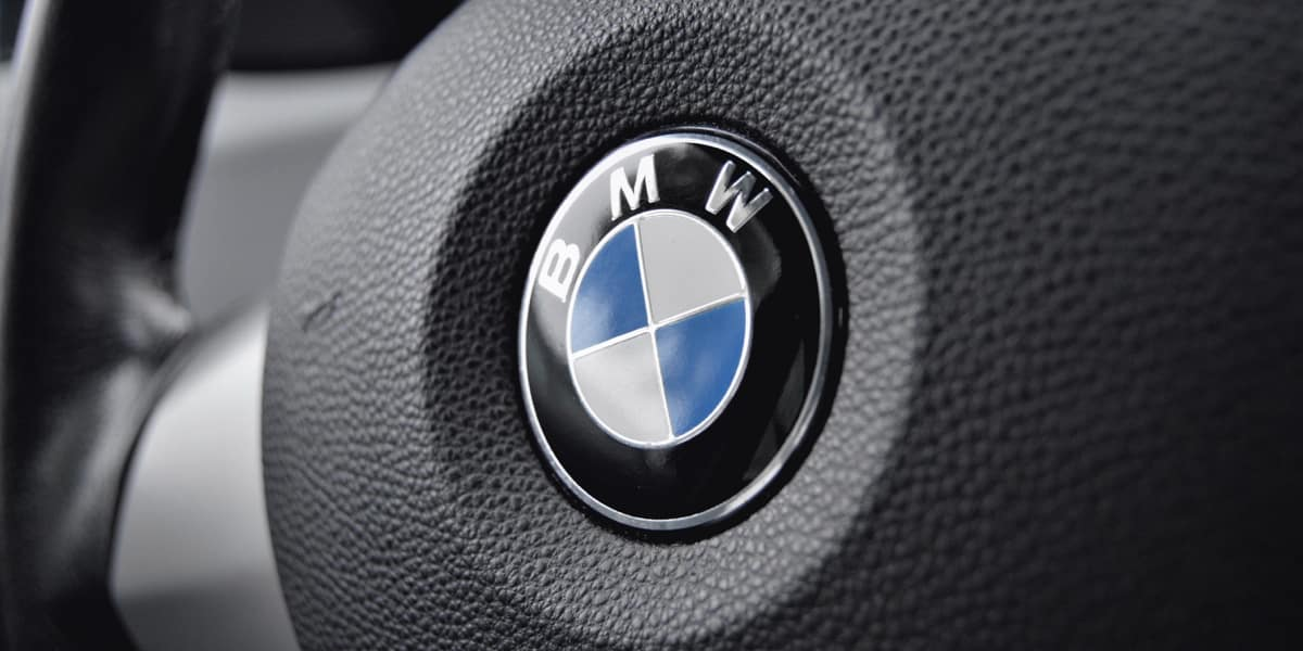 Black and white photo of a close up steering wheel with BMW emblem in focus.