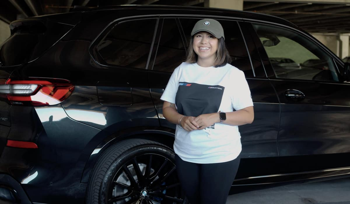 Daffne Gaitan standing in front of a black polished BMW X5 inside of a garage.
