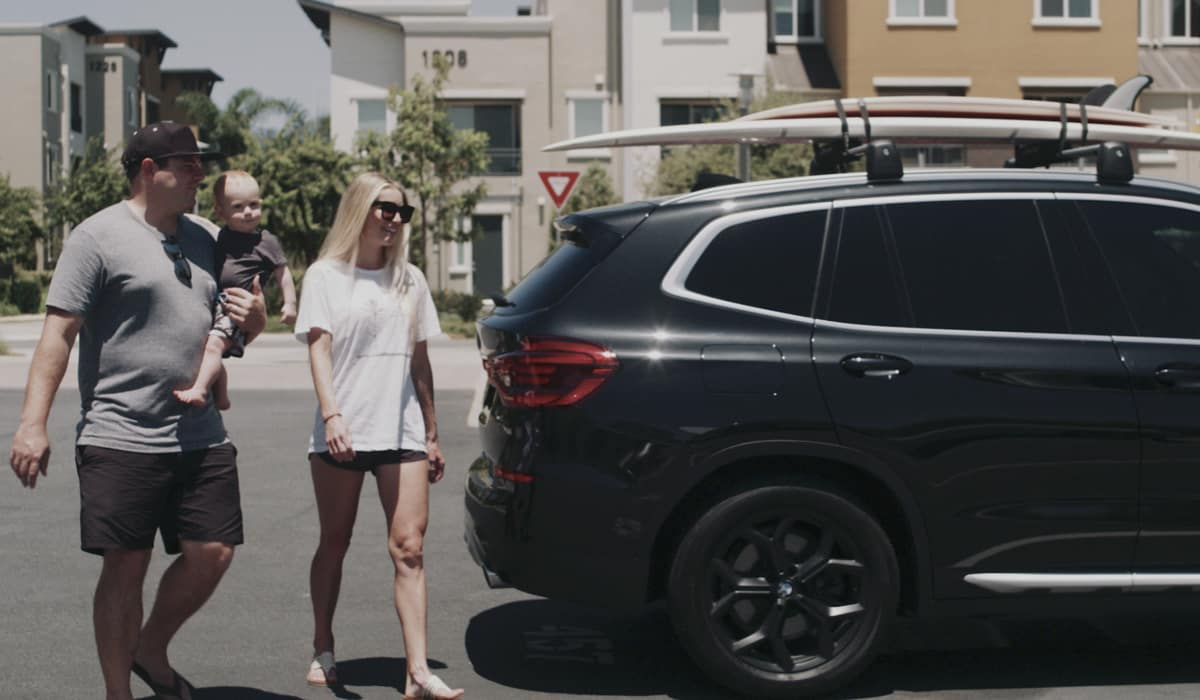 Brecht family walking in beach clothes to their new BMW X3 in black with surfboards on their rack.