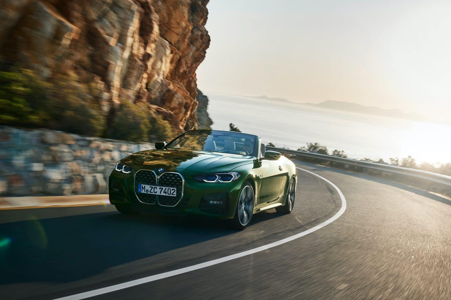 New BMW 4 Series convertible driving on a winding road near the ocean.