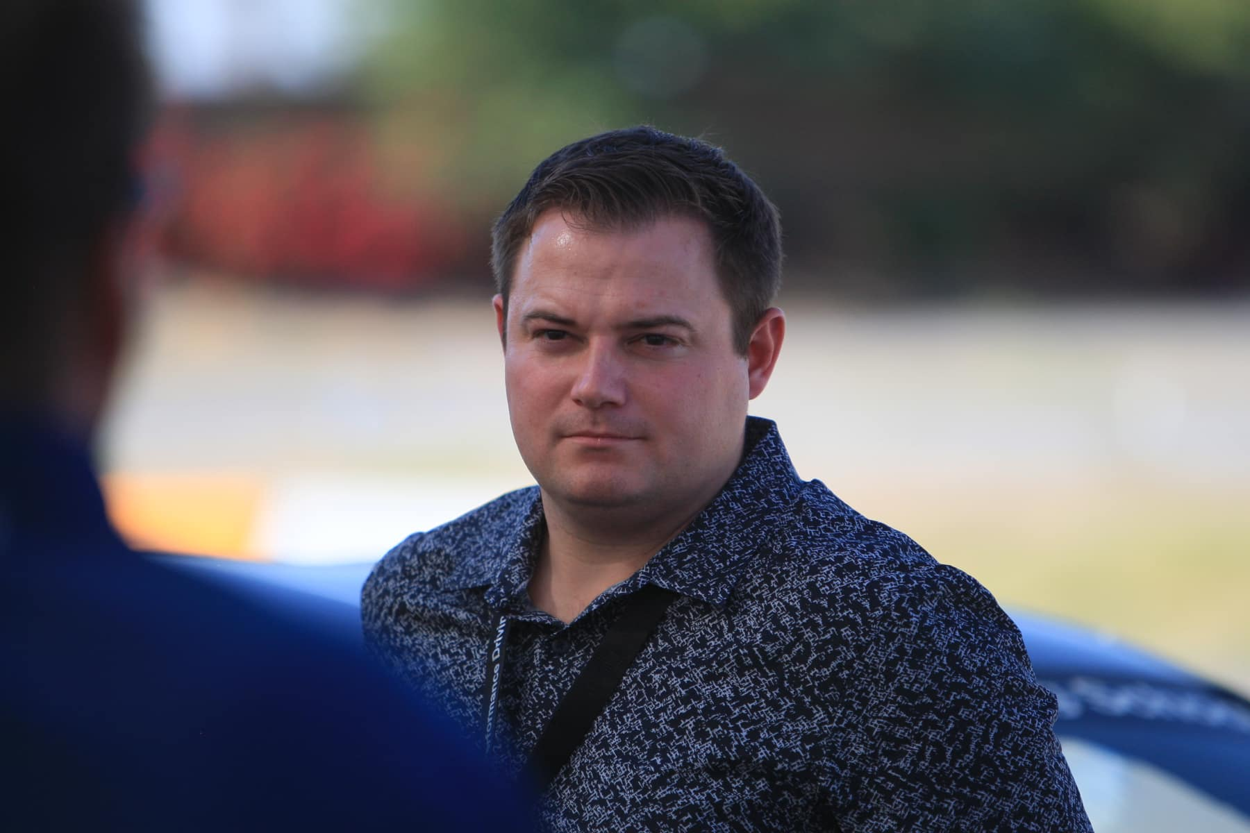Photo of Peter Brecht, looking all pensive at a BMW Race Day at Thermal. Super snazzy button up blue shirt.
