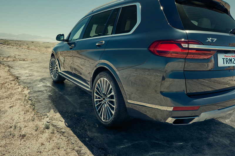 BMW X7 driving on a dirt road. Shot from the rear.