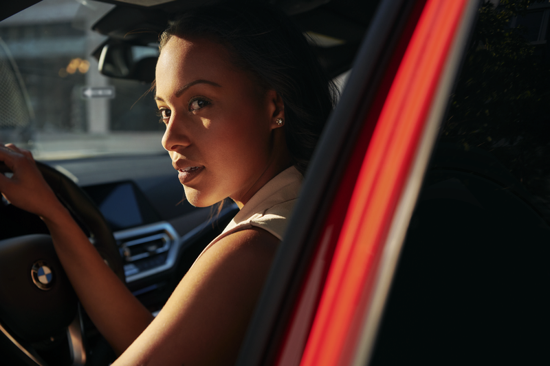 Young woman in a BMW, looking back over her shoulder.