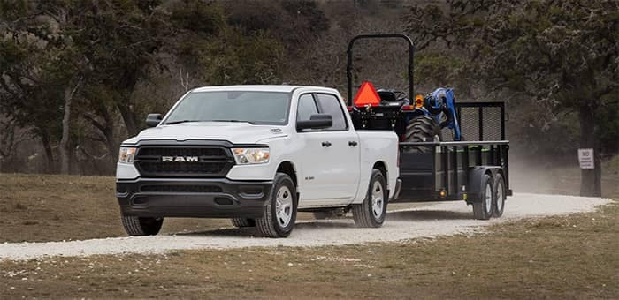 Ram 1500 towing a trailer with a tractor