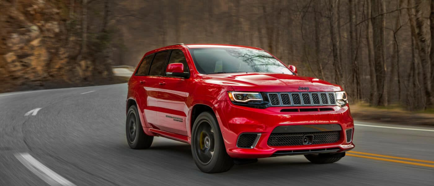 2020 Jeep Grand Cherokee in red driving on a highway in the forester
