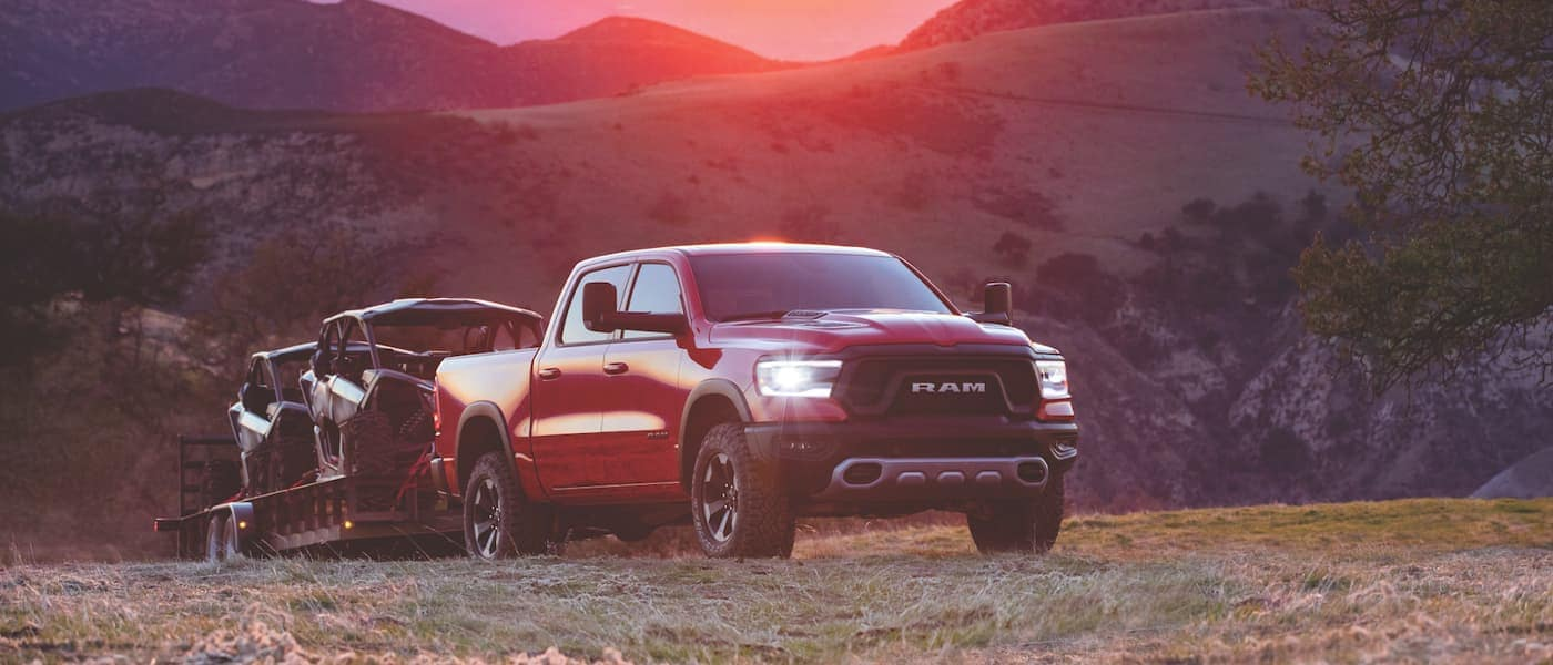 2020 Ram 1500 driving over a hill towing boats during sunset