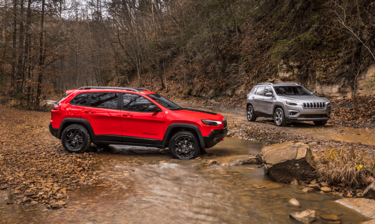 Two 2021 Jeep Cherokee's offroad parked in stream