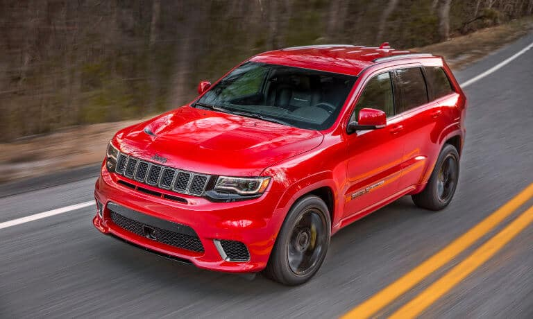 2021 Jeep Grand Cherokee exterior driving along forest highway