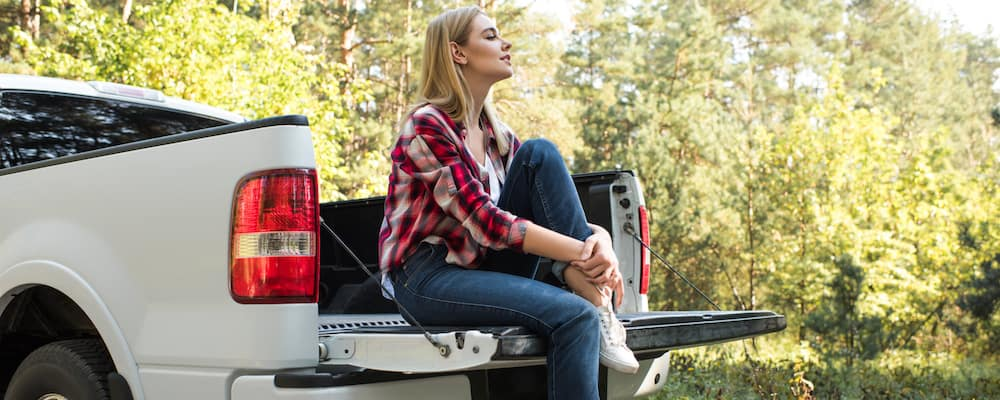 A woman sits on the back of a truck bed in a forest clearing, looking off into the distance.