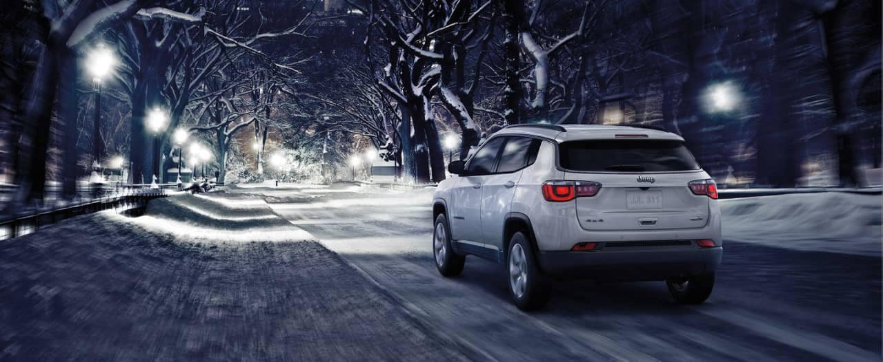 Jeep Compass driving down street in winter