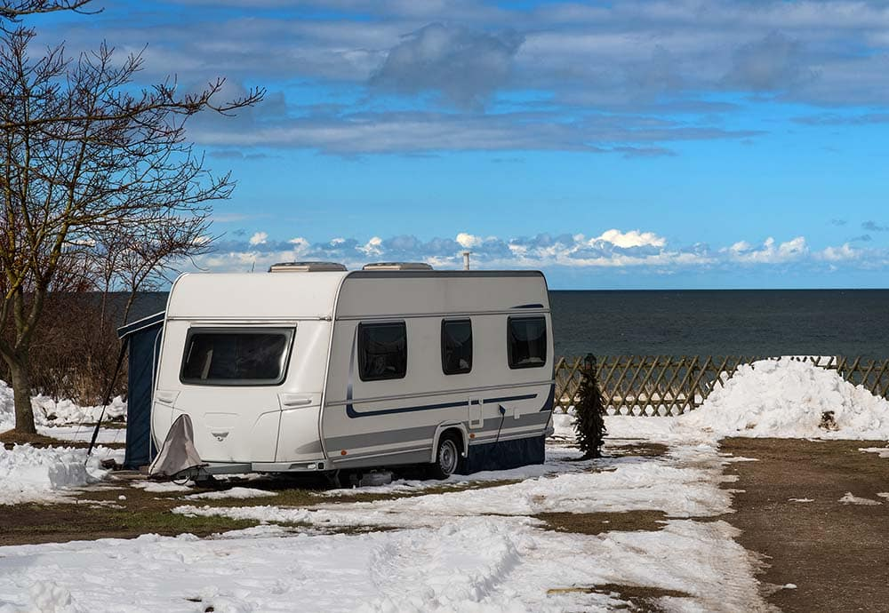 RV in snow by lake