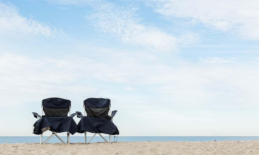 Two beach chairs on the beach of Pacific Ocean.