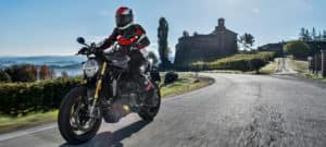Motorcyclist riding Monster 1200S down scenic road