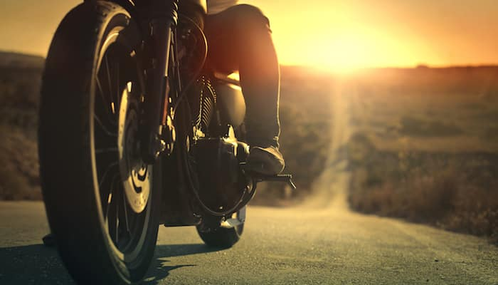 Closeup of bottom half of motorcycle, with rider's foot on footrest, with the open road in the background at sunset