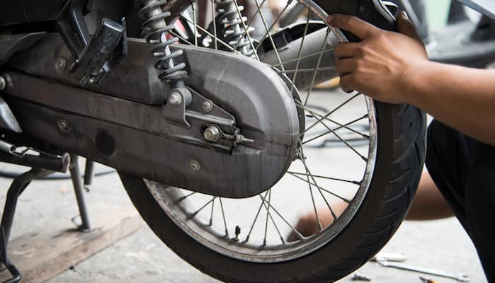 Mechanic's hand on rear tire of motorcycle prior to changing it