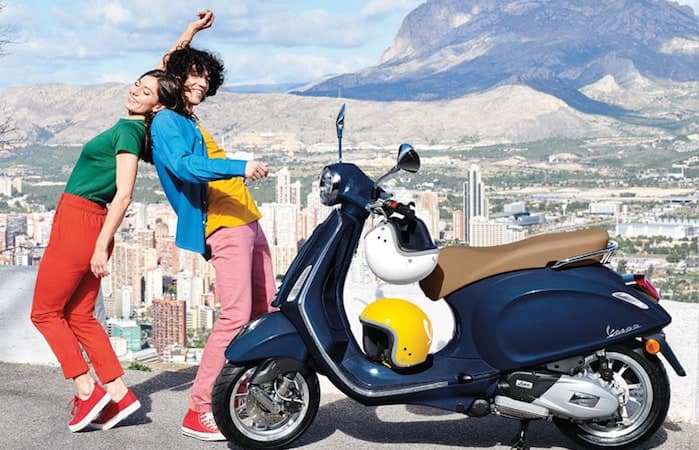Couple standing and smiling near parked Vespa with mountains in background