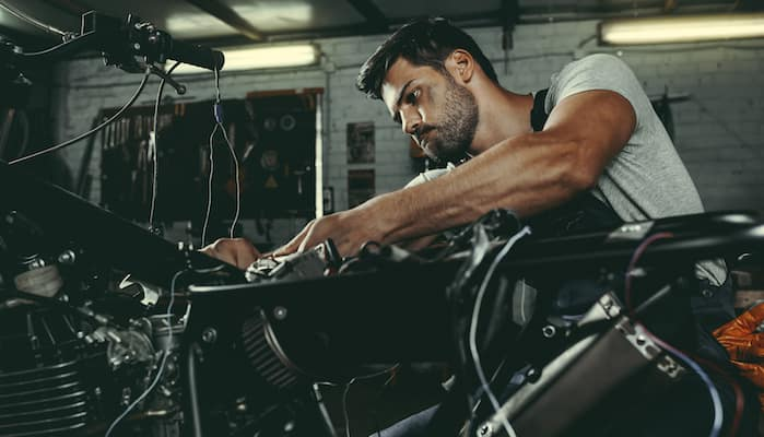 Mechanic working on servicing motorcycle in repair shop