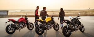 Three Ducati Monster motorcycles lined up while riders stand nearby overlooking the beach