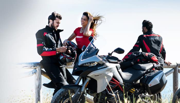 Smiling woman and two men stand near parked Ducati motorcycles