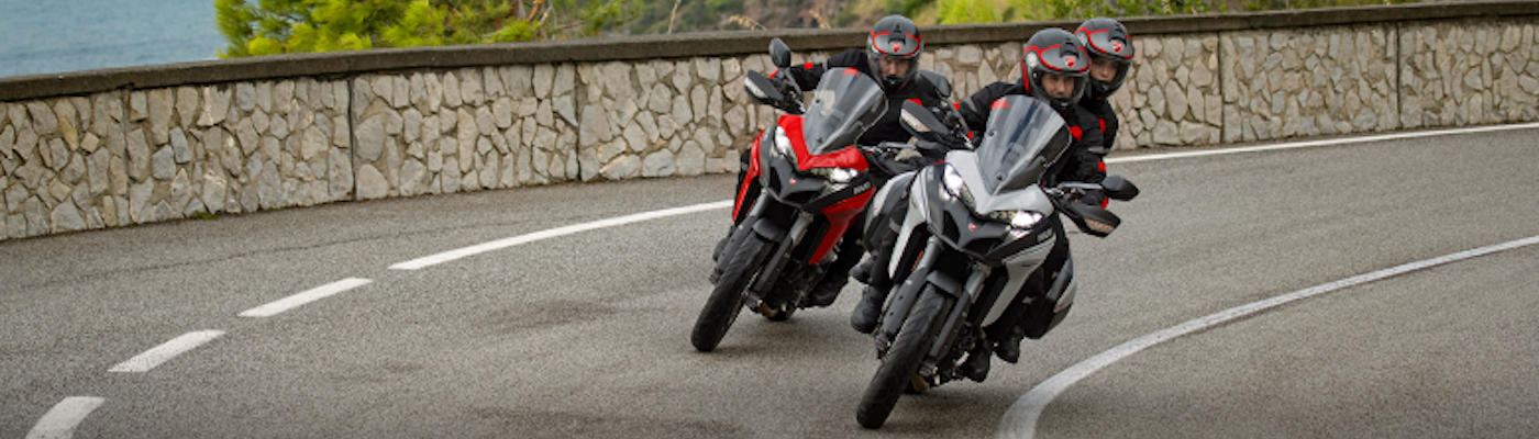 Three people riding Ducati motorcycles around a curve on the highway