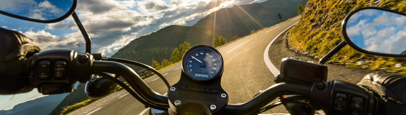 First-person POV of riding along curve in highway on motorcycle