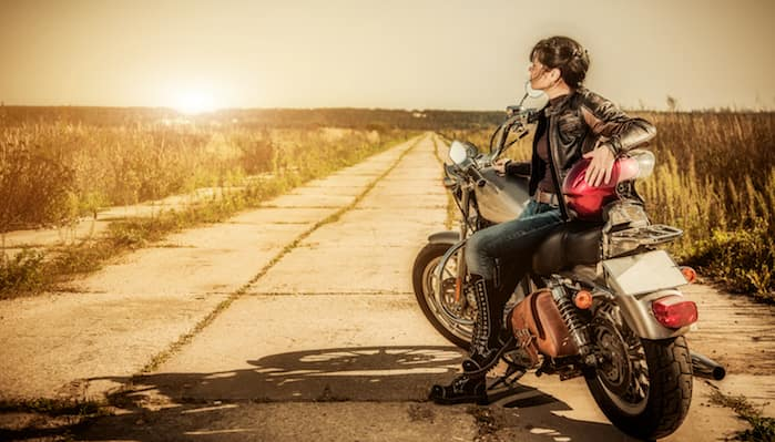 Woman sitting on parked motorcycle along side of road at dusk