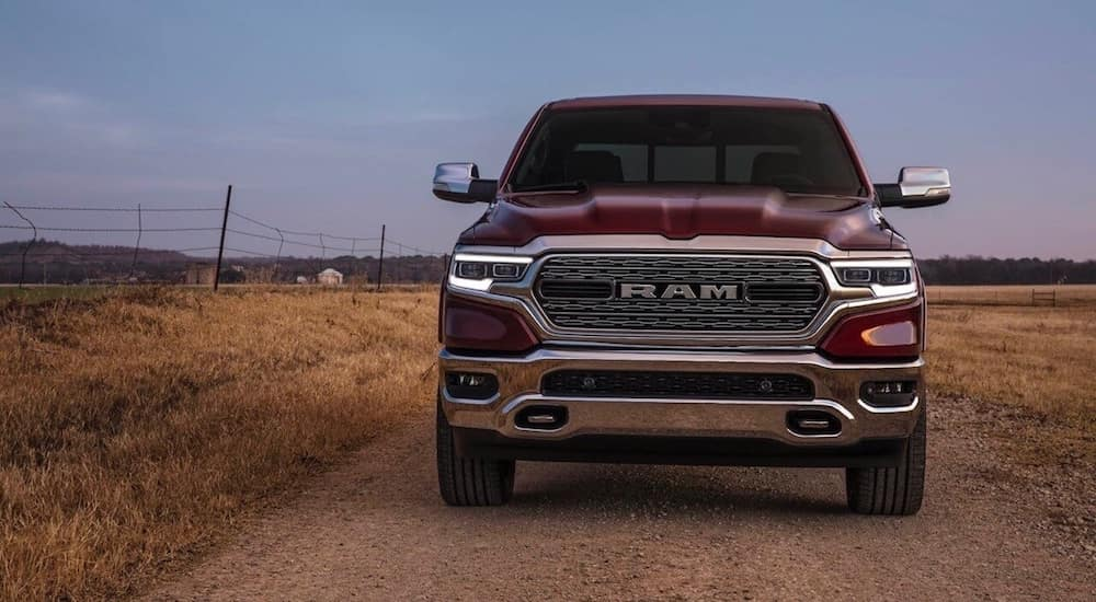 A red 2019 Ram truck from the front on a dusty dirt road at dusk with a barbed wire fence