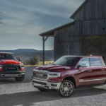 A pair of red 2019 RAM 1500 next to a barn in Ennis TX