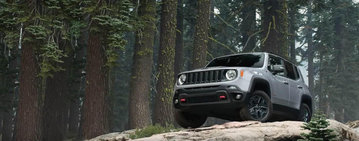 A silver 2019 Jeep Renegade climbing over a rock on a Texas trail