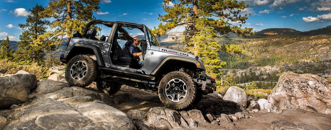 A silver 2015 Jeep Wrangler Rubicon rock climbing over rocks
