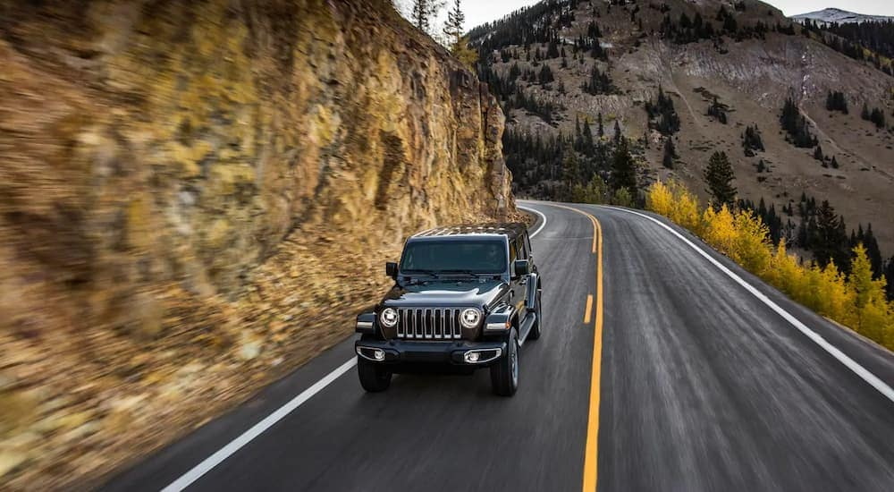 A black 2019 Jeep Wrangler driving along a cliffside with mountains and yellow trees in the distance