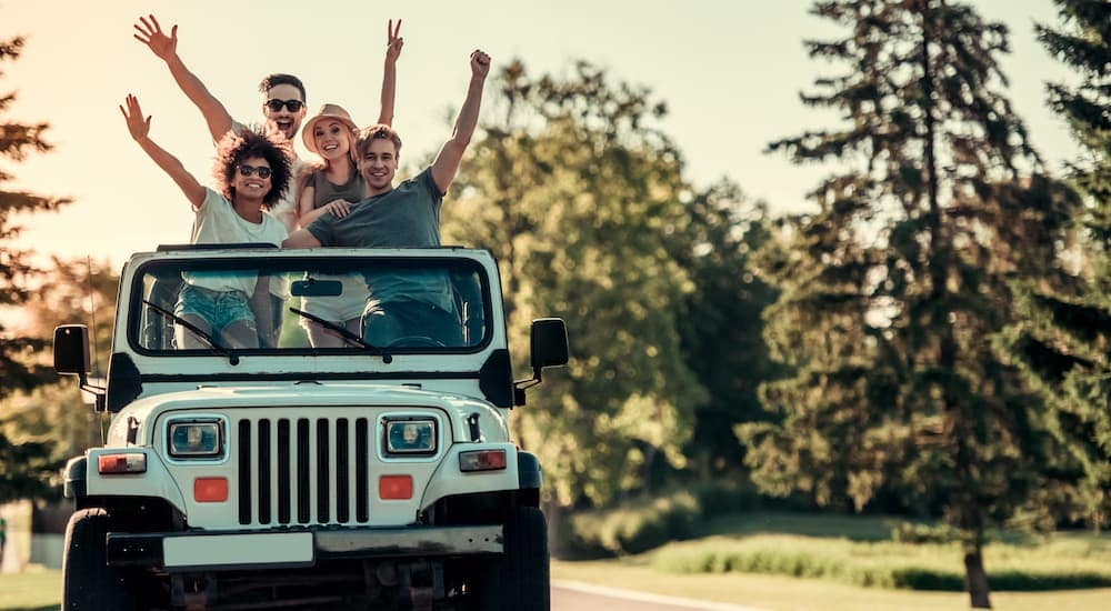 Four friends standing in a white Jeep Wrangler waving, from the front