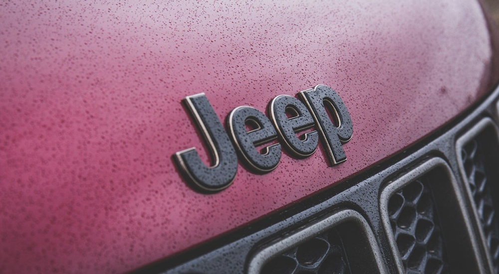 The image shows the Jeep emblem on a burgundy 2019 Jeep Grand Cherokee covered in rain drops.