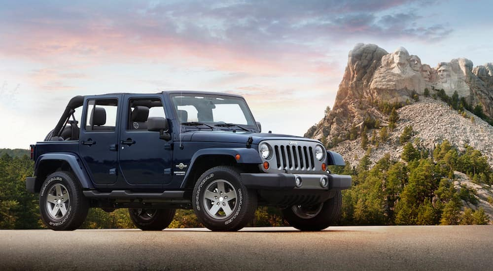 A dark blue 2015 Jeep Wrangler Unlimited in front of a majestic mountain at sunset