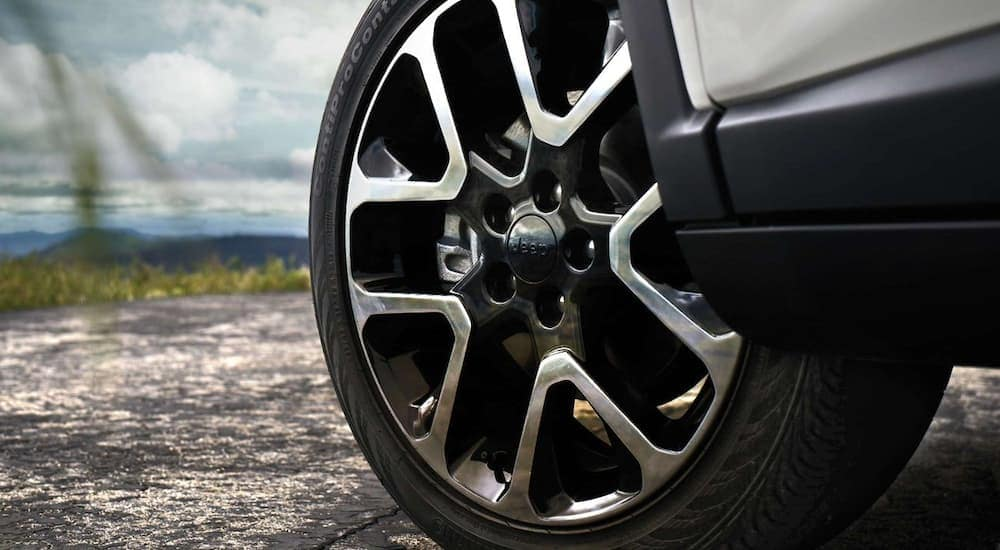 A close up of the tire on a 2019 Jeep Compass is shown overlooking a mountain. A Jeep lease is a great way to get into a new Jeep.
