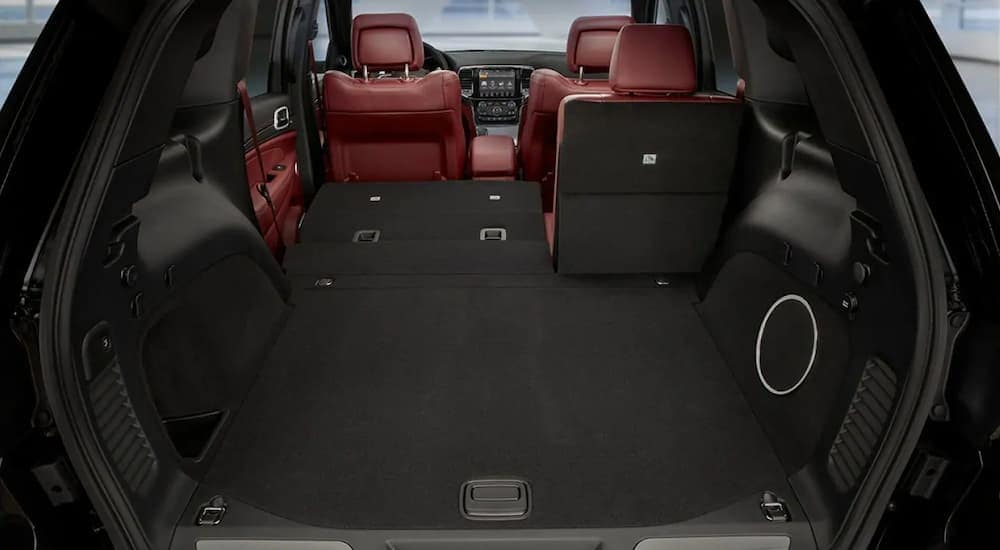 The black and red interior of a 2019 Grand Cherokee is shown from the cargo area. Check out the Jeep lease deals in Ennis, TX.