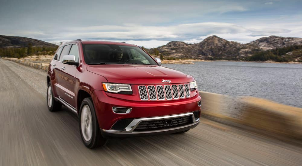 A red 2014 Jeep Grand Cherokee is driving along a body of water with mountains in the distance. Check out this model year used Jeep Grand Cherokee.