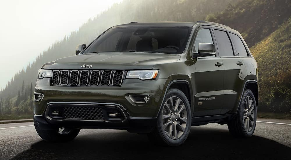 A green 75th Anniversary 2016 used Jeep Grand Cherokee is parked on a mountain road with haze behind it.