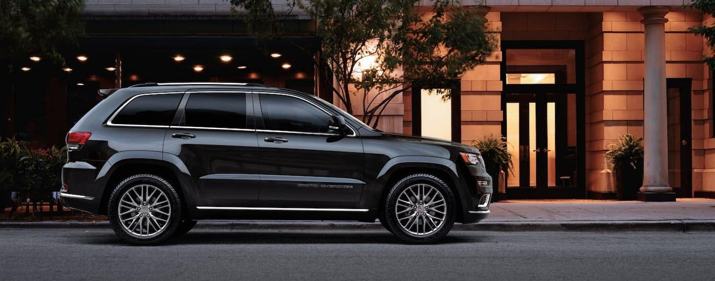 A black 2018 Jeep Grand Cherokee is parked on a dark city street.