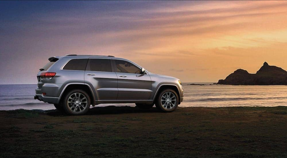 A silver 2018 Jeep Grand Cherokee is on the beach at sunset.