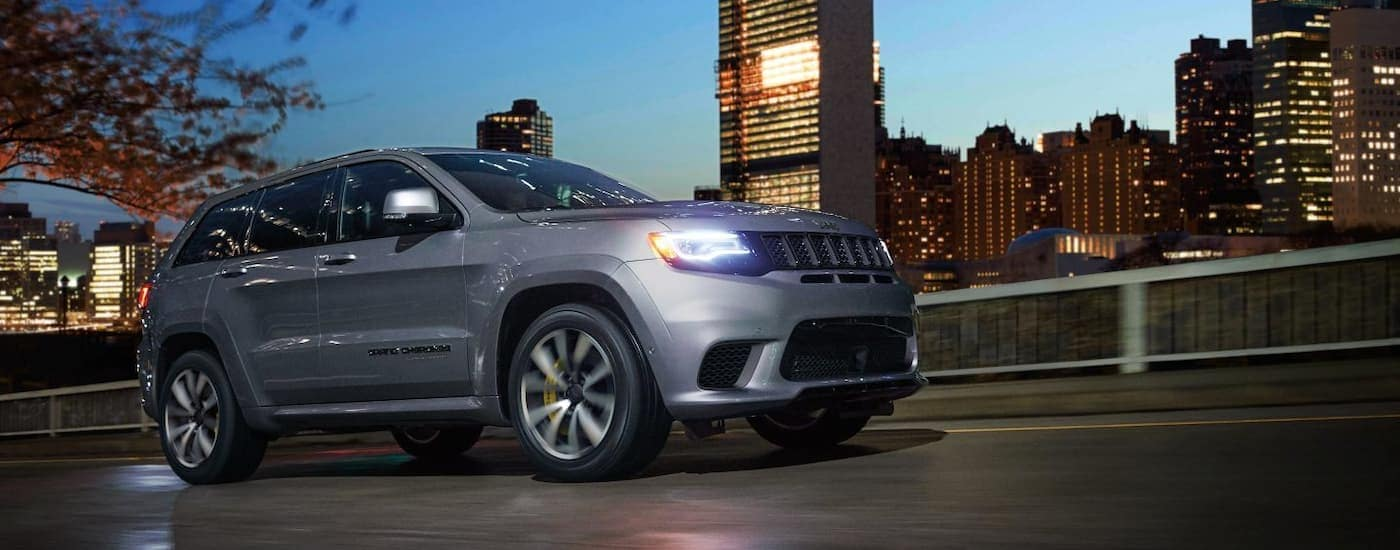 A silver 2018 Jeep Grand Cherokee is driving through a city as dusk.