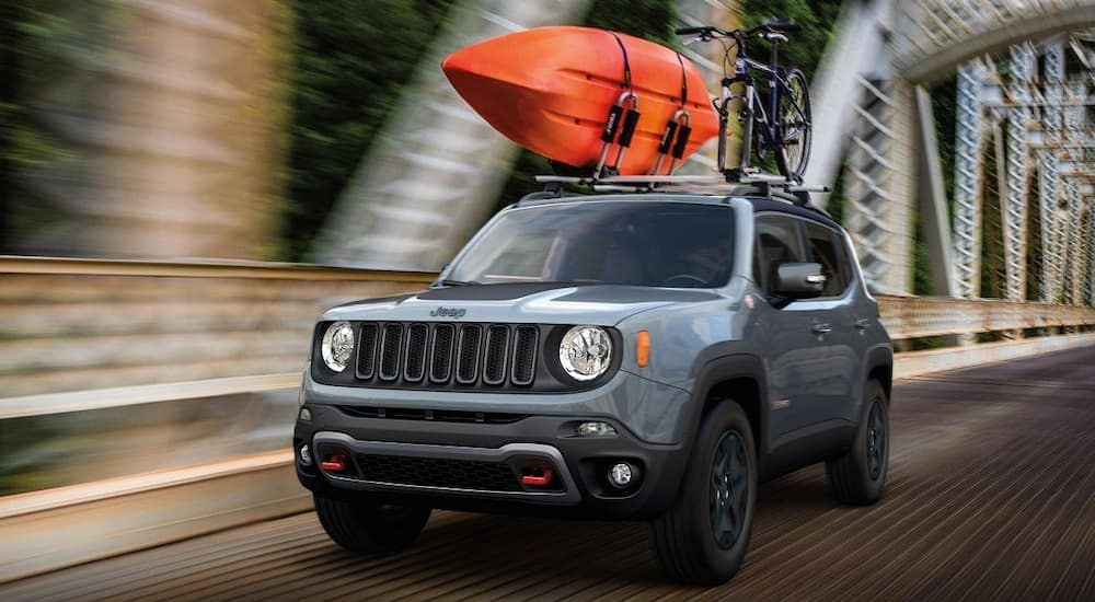 A grey 2018 Jeep Renegade is passing over a bridge with a kayak and a bike on the roof. Find used Jeeps for sale in Ennis, TX at Frank Kent CDJR.