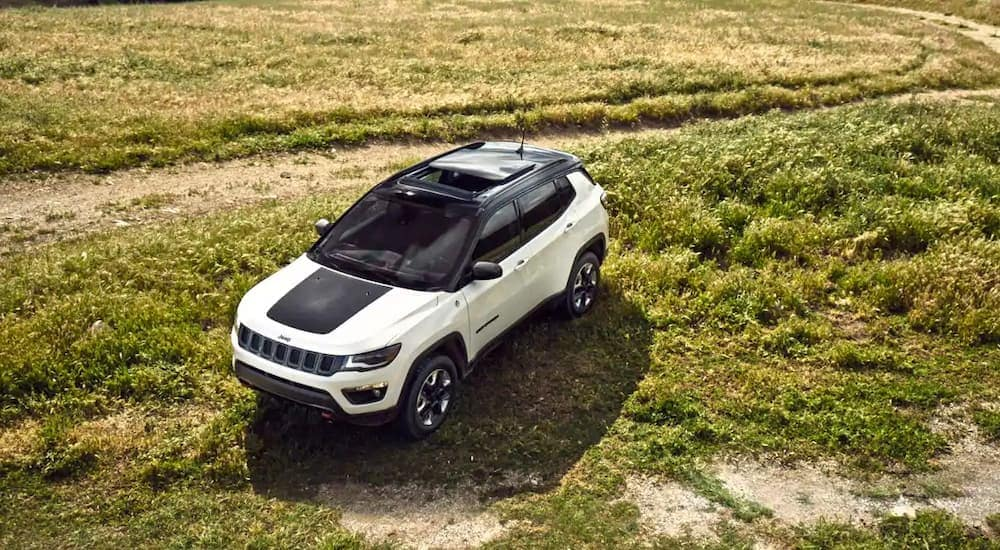 A white and black 2018 Jeep Cherokee is shown in a field in Ennis, TX.