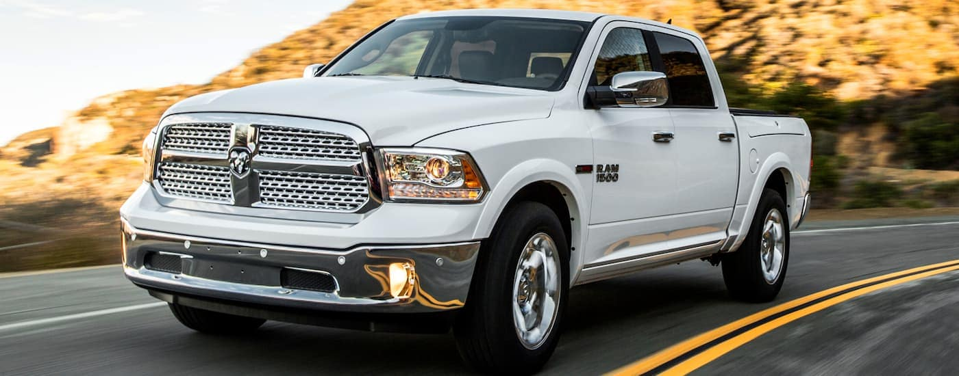 A white 2014 used Ram 1500 is driving on a mountain road.