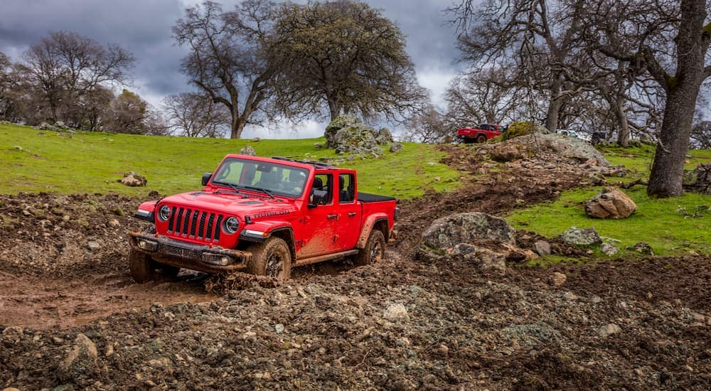 A red 2020 Jeep Gladiator is in the mud on a trail near Ennis, TX.