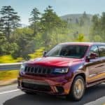 A red 2019 Jeep Grand Cherokee is shown driving down a highway with trees and mountains in the background near a Jeep dealership in Dalles, TX.